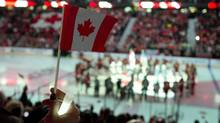 A woman holds up a Canadian flag as the national anthem is played during pre-game ceremonies at the NHL game between the Ottawa Senators and New Jersey Devils Saturday October 25, 2014 in Ottawa. THE CANADIAN PRESS/Adrian Wyld (Adrian Wyld/THE CANADIAN PRESS)