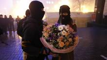 An activist from an anti-government protest group presents a bouquet of flowers to his girlfriend in front of fellow activists near the site of previous clashes with riot police in Kiev on Feb. 13, 2014. (REUTERS)