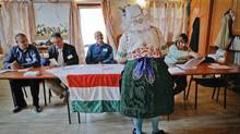 A Hungarian woman in traditional dress votes in her country's recent referendum on migration. (Vadim Ghirda/AP)