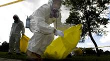 Workers clean up asbestos particles in a Toronto park in 2008 after a nearby blast. (SAMI SIVA/THE GLOBE AND MAIL)