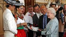 The Queen is given a sombrero from the Delfines Marching Band and Dancers during a tea party for the cast of the Diamond Jubilee Pageant at Windsor Castle, England Friday May 11, 2012. (Steve Parsons/Steve Parsons / AP)