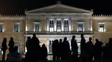 Protesters stand in front of the parliament in Athens Friday as law makers prepare for a confidence vote on the government of Prime Minister George Papandreou. (YANNIS BEHRAKIS/REUTERS)