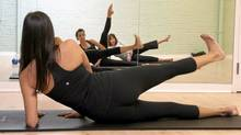 Shalini Bhat leads a Ballet-core class for students Martine Magion and Lynn Selby. Ballet-core is a ballet and Pilates hybrid class that begins with standing ballet exercises and ends with Pilates mat work (Sarah Dea for The Globe and Mail)