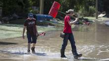Josh Lynen, 15, along with his brother Connor, 14, make their way through the Calgary neighbourhood of Bowness June 23, 2013 which was flooded by the Bow river look for driveways to shovel out. (John Lehmann/The Globe and Mail)