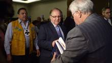 Truth and Reconciliation Commission Chairman Justice Murray Sinclair, right, hands a copy of the commission's main report on Canada's residential school system to then-Aboriginal Affairs Minister Bernard Valcourt, centre, as Assembly of First Nations Nations Chief Perry Bellegarde looks on June 2, 2015.