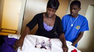 Clemee Joseph and her 13-year-old son, Kasim St. Remy, display several T-shirts with pictures of Jarvis.