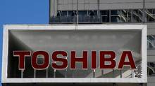 The logo of Toshiba Corp. is seen as window cleaners work on the company's headquarters in Tokyo, Japan, February 14, 2017. Toshiba Corp.'s plans to sell its memory-chip business to raise much-needed cash hit a snag as joint-venture partner Western Digital Corp. said the sale may violate the companies' contract. (Toru Hanai/REUTERS)