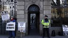 A man protests outside a government building in Dublin on Wednesday, Nov. 24, 2010. The Irish government announced €15-billion of spending and tax cuts. (CATHAL MCNAUGHTON/Cathal McNaughton/Reuters)