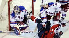 Washington Capitals center Brooks Laich (21) gets tripped up in front of New York Rangers goalie Henrik Lundqvist (30) and defenseman Anton Stralman (32) during the first period of Game 3 of their NHL hockey Stanley Cup second-round playoff series at the Verizon Center in Washington, Wednesday, May 2, 2012. (AP)
