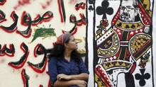 A woman looks at a graffiti with Egyptian President Mohamed Morsi's face on a playing card near Tahrir Square in Cairo. (AMR ABDALLAH DALSH/REUTERS)