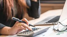 Close up of female accountant or banker making calculations. Savings, finances and economy concept (Getty Images/iStockphoto)