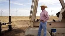 Texan Louis Brooks stands near an old oil pump and dozens of wind turbines, in background, on his property in Sweetwater. Last year Texas generated twice the amount of electricity from wind than all of Canada. (Brian Harkin/The New York Times)