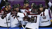 Latvia forward Lauris Darzins is congratulated by teammates after scoring against Switzerland in the third period of a men's ice hockey game at the 2014 Winter Olympics, Tuesday, Feb. 18, 2014, in Sochi, Russia. Latvia won 3-1 to advance to the quarterfinals. (Julio Cortez/AP)