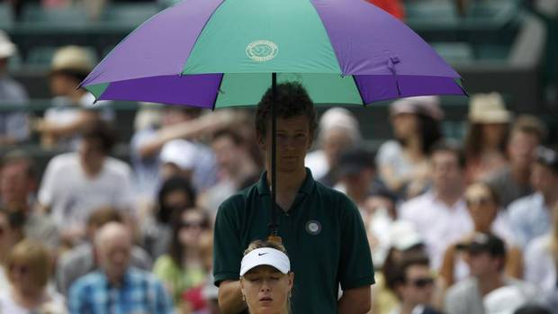 A ball boy holds an umbrella over Maria Sharapova (STEFAN WERMUTH/REUTERS)