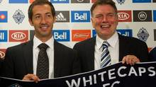 Vancouver Whitecaps' President Bob Lenarduzzi, right, and Martin Rennie, of Scotland, pose for photographs after Rennie was introduced as the new head coach of the MLS soccer team beginning with the 2012 season in Vancouver, B.C., on Tuesday August 9, 2011. (Darryl Dyck/The Canadian Press)