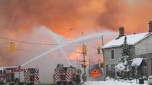 Firefighters battle a major fire in downtown Kingston on Dec. 17, 2013. (LARS HAGBERG/THE CANADIAN PRESS)