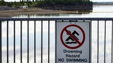 A no swimming sign along the banks of the Gleniffer reservoir while a boom stretches out to contain a pipeline leak on the lake near Innisfail, Alta., Tuesday, June 12, 2012. (Jeff McIntosh/THE CANADIAN PRESS)