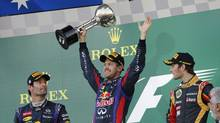 Red Bull driver Sebastian Vettel of Germany (center) celebrates with the trophy after winning the Japanese Formula One Grand Prix at the Suzuka circuit in Suzuka, Japan, Sunday, Oct. 13, 2013. At left is second place Red Bull driver Mark Webber of Australia, and at right third placed Lotus driver Romain Grosjean of France. (Shizuo Kambayashi/AP Photo)