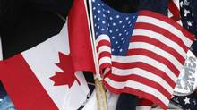 A woman holds U.S. and Canadian flags in Ottawa. (CHRISTINNE MUSCHI/REUTERS)