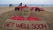 Visitors gather near a sculpture of Formula One great Michael Schumacher by sand artist Sudarshan Patnaik at a beach in Puri, in the eastern Indian city of Bhubaneswar, India (Biswaranjan Rout/The Associated Press)