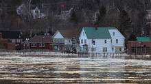 Water and ice from the St. John River flows on to the roadway in the small western New Brunswick community of Perth-Andover on Saturday, March 24, 2012. The village has issued an evacuation order to residents living in low lying areas and declared a state of emergency in the face of the rising water levels. (Mike Dembeck/The Canadian Press/Mike Dembeck/The Canadian Press)