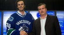 Vancouver Canucks' goalie Ryan Miller, left, shakes hands with general manager Jim Benning as they stand for photos during a news conference after Miller signed a three-year contract with the NHL hockey team in Vancouver, B.C., on Tuesday July 1, 2014. (The Canadian Press)