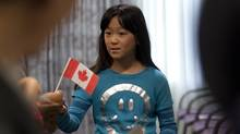 Mengyi Fu, 10 receives, a Canadian flag as her parents Jing Shan Fu and mom Mao Qiong Lin watch during a Canadian Citizenship ceremony in Ottawa on Sept. 29, 2010. (Pawel Dwulit/Pawel Dwulit for the Globe and Mail)