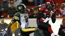 Calgary Stampeders' Keon Raymond (R) intercepts a pass intended for Edmonton Eskimos' Fred Stamps during the second half of their CFL football game in Calgary, Alberta, September 28, 2012. (Reuters)