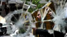 A Greek man is reflected in a broken mirror as he checks newspapers in the center of Athens (DIMITAR DILKOFF/AFP/Getty Images)
