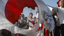 Anti-Japan protesters burn a Japanese flag in Wuhan, in central China's Hubei province,on Sept. 16, 2012. (AP)