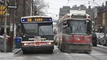 A shuttle bus beside a stalled streetcar at the intersection of Queen St. East and Sumach St. on March 1. A power outage left thousands of commuters scrambling to find other means of transportation during morning rush hour. (Fred Lum/The Globe and Mail)