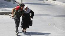 A Free Syrian Army fighter helps a woman to run across a street during clashes in Aleppo on August 12, 2012. (GORAN TOMASEVIC/REUTERS)