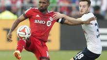 Toronto FC's Jermain Defoe, left, and Tottenham Hotspur's Ryan Mason battle for the ball during the first half of a friendly soccer match in Toronto on Wednesday, July 23, 2014. (Darren Calabrese/THE CANADIAN PRESS)