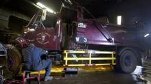 A Public Works mechanic works on a dump truck which has been retrofitted with side guards, in their garage in Westmount, Que., Nov. 29, 2011. (Christinne Muschi For The Globe and Mail)