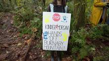 A protester carries a sign on a trail on Burnaby Mountain in Burnaby, B.C., on Oct. 29, 2014. (DARRYL DYCK/THE CANADIAN PRESS)
