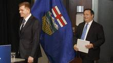 Wildrose leader Brian Jean, left, and PC Leader Jason Kenney, seen arriving at a news conference in Edmonton on Thursday, will have to overcome a great divide in policies to merge their respective parties. (JASON FRANSON/THE CANADIAN PRESS)