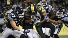 Edmonton Eskimo Weldon Brown is tackled by Toronto Argonauts during a CFL Eastern semi-final game between the Argonauts and the Eskimos at the Rogers Centre on Nov 11 2012. (Fred Lum/The Globe and Mail)