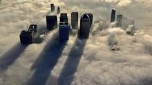 Canary Wharf, east of the City of London, peeks out of an early morning fog. The project -- the most daring of Paul Reichmann's Olympia & York -- sank the company under a sea of debt. (REUTERS)