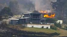 A house is seen on fire in the Tasmanian town of Dunalley, in this still image taken from video shot Jan. 5, 2013. Bushfires in the Tasmanian town of Dunalley have destroyed up to 80 homes, and at least one person is feared dead. Hundreds have now left the area as the fires continue to spread on the east of the Australian island state. (REUTERS TV/Reuters)