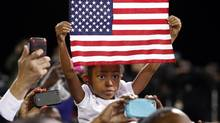 A young girl holds a flag aloft as U.S. President Barack Obama speaks during a campaign rally in Las Vegas, Nevada October 24, 2012. (KEVIN LAMARQUE/REUTERS)
