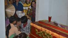"""Relatives mourn next to the coffin of Vietnamese fisherman Dang Gium at his house in Ly Son island in Vietnam's central Quang Ngai province May 27, 2014. Gium was killed while one of his colleagues disappeared when their boat was rammed by a """"strange"""" vessel on Sunday, a Vietnamese official said. REUTERS/Stringer (VIETNAM - Tags: POLITICS CIVIL UNREST MARITIME OBITUARY) (STRINGER/VIETNAM/REUTERS)"""