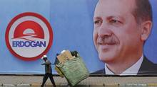 A garbage recycler pushes his cart as he passes by an election campaign banner of Turkey's Prime Minister and presidential candidate Tayyip Erdogan in Istanbul August 7, 2014. Turkey holds its first direct presidential election on Sunday, with Prime Minister Erdogan aiming to become head of state after dominating Turkish politics for more than a decade. REUTERS/Murad Sezer (TURKEY - Tags: POLITICS ELECTIONS) (MURAD SEZER/REUTERS)