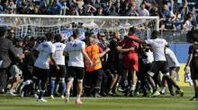 Bastia's supporters invade the pitch to try to fight with Lyon's Portuguese goalkeeper Anthony Lopes (in red) and players during their warm up prior to the French L1 Football match between Bastia and Lyon on April 16, 2017, at the Armand Cesari stadium, in Bastia, on the French Mediterranean island of Corsica. (PASCAL POCHARD-CASABIANCA/AFP/Getty Images)