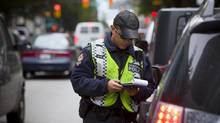Vancouver police constable Alex Chow pulls over drivers caught on their cellphones on Hornby Street in Vancouver in September 2013. (Ben Nelms for The Globe and Mail)