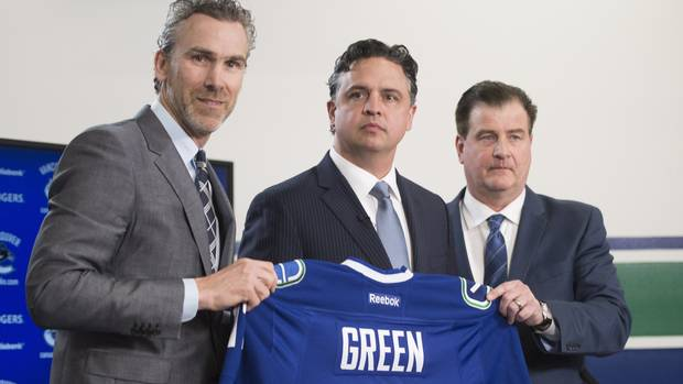 Vancouver Canucks president Trevor Linden, left, and general manager Jim Benning, right, introduce new Canucks head coach Travis Green in Vancouver on Wednesday.