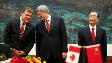 Canadian Foreign Affairs Minister John Baird, left, confers with Prime Minister Stephen Harper in Beijing on Wednesday while standing beside Chinese Premier Wen Jiabao. (Diego Azubel/Associated Press)