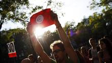 A protester holds a poster of a euro sign during an anti-Merkel demonstration in Madrid Sept. 6, 2012. (SUSANA VERA/REUTERS)