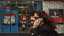A woman talking on her cell phone walks past a Verizon store in Manhattan. (JENNIFER SZYMASZEK/AP)