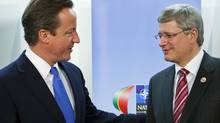 Prime Minister Stephen Harper meets British counterpart David Cameron at the NATO summit in Lisbon on Nov. 20, 2010. (Sean Kilpatrick/The Canadian Press)