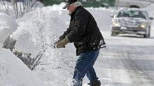 A resident clears his sidewalk in Dartmouth, N.S. on Sunday, Feb. 10, 2013. A major winter storm swept through Atlantic Canada on the weekend causing power outages, disrupting travel and forcing event cancellations. (Andrew Vaughan/THE CANADIAN PRESS)